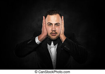 Man covering his ears - Man in suit covering his ears over...