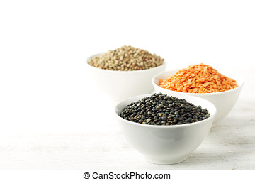 Bowls of assorted dried lentils with red lentils, black beluga lentils and mountain lentils