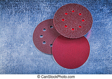 Sanding wheels holder on metallic background directly above