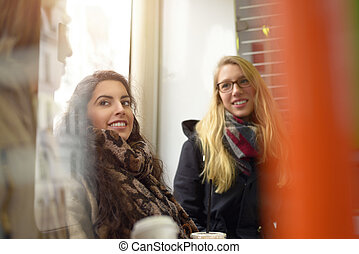 Female friends talking in public space by window - Blond and...