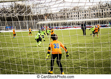 boys kicking football goalkeeper in gate on the sports field