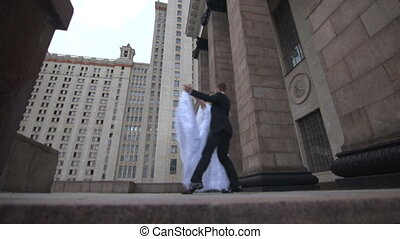Bride and groom dancing on the background of the building on the street