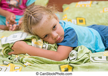 Little girl sitting on a double bed and frightened looks...