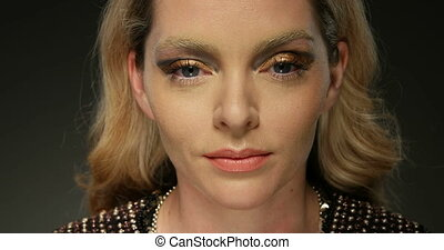 face close-up - pretty woman with gold makeup with mirror...