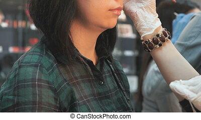 Master girl making eyebrows correction at salon