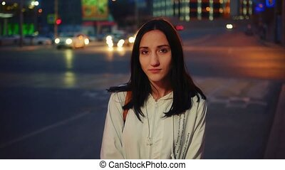 Young caucasian woman in city at night serious face portrait...