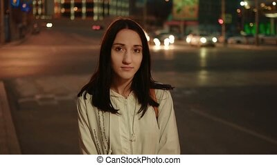 Young woman in city at night serious face portrait on...
