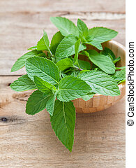 Closeup fresh peppermint leaves in the wooden bowl on rustic...