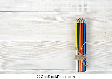 Set of sharp colorful pencils tied with wool rope on a...