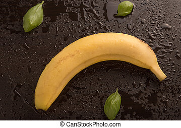 Banana and basil leaves on dark wet background