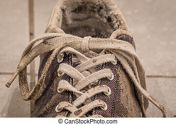 Close-up of laces on a dirty shoe