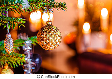 Christmas tree with a golden bauble and candlelights