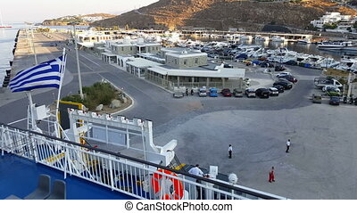 Mykonos, Greece - New port (summer). Greek flag on a ship...