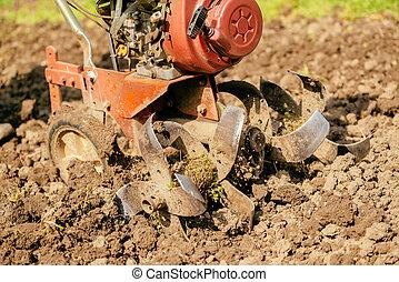 Preparing garden soil with cultivator tiller, new seeding...