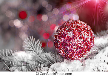Christmas decoration ball on snowy fir brench on red...