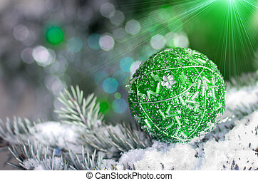 Christmas decoration ball on snowy fir brench on green and...