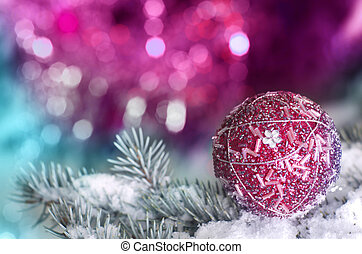 Christmas decoration ball on snowy fir brench on pink and...