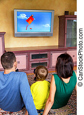 television family at - family sitting in front of a tv and...