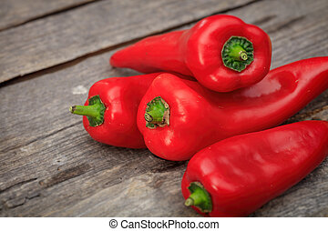 Stack of red pointy peppers, on wooden surface