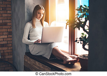 Surfing net at home. Beautiful young woman using her laptop...