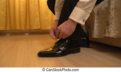 The man wears shoes, tying laces closeup in motion