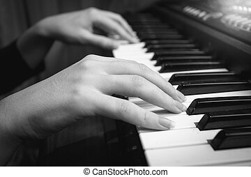 Black and white closeup of female hands on digital piano...