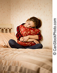 Depressed girl sitting on bed and embracing cushion -...
