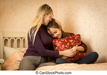 Mother embracing and solacing teenage daughter at bedroom -...