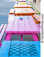 Colorful Picnic Tables with Checkerboards - A line of...