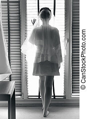 Black and white photo of sexy bride looking out of window -...