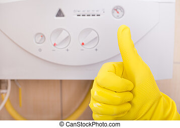 Thumb up in front of gas boiler - Close up of human hand...