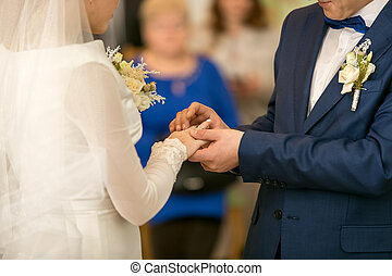 Young groom putting wedding ring on brides finger - Closeup...
