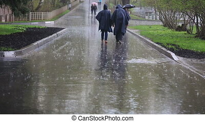 Moscow street with pedestrians walking under the rain -...
