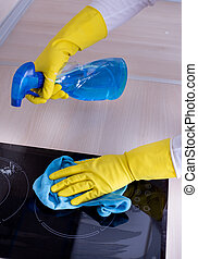 Induction hob cleaning - Close up of human hand with...