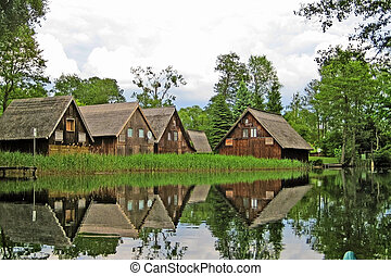Boat houses - brown wooden boathouses reflecting in the...