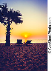 Silhouette palm tree on the beach with empty chair at sunset...