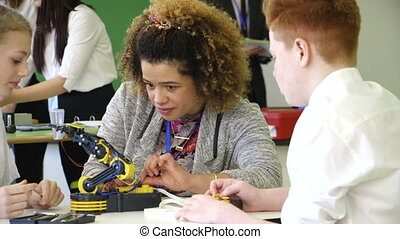 Students building a robotic arm - Students are learning...