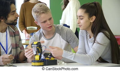Students building a robotic arm - Young, male teacher...