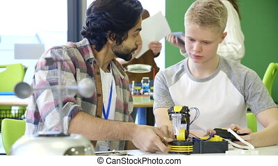 Building a robotic arm - Young, male teacher helping his...