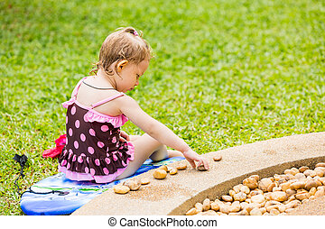 Cute little child girl in a swimsuit playing with stones on...