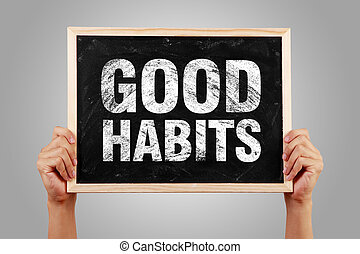Good Habits - Hands holding small blackboard with text Good...