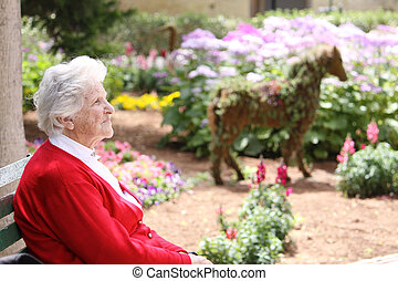 elderly woman sitting in the sun