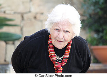 hunch back old woman - an old caucasian woman bending down...