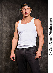 athletic guy in a vest and baseball cap - athletic guy in a...
