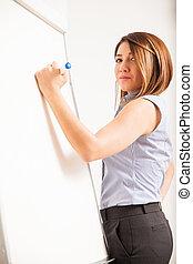 Cute female tutor writing on a whiteboard