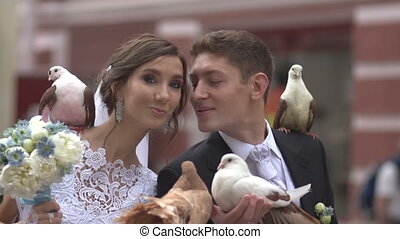 Kiss newlyweds with pigeons in hands