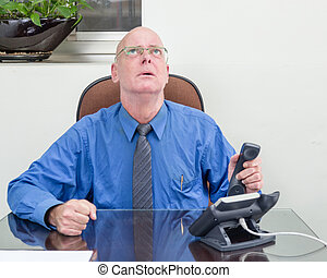 Businessman on phone at desk, frustrated - Frustrated...
