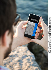 Man with sunglasses using calculator on the smartphone near...