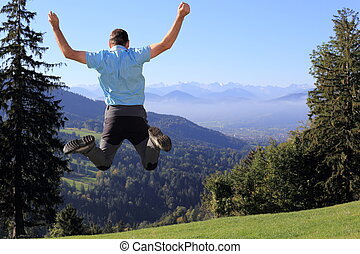 jumping up in spring time - happy man is jumping up in...
