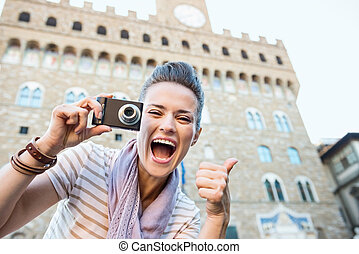 Woman tourist with photo camera showing thumbs up, Florence...